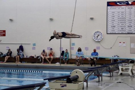 "Junior Jenna Steffl performs a back somersault with one and a half twists at a diving meet. Steffl finished the regular season with a record of 8-0 and has already set high goals for her senior season. ""I hope to get better, bigger dives in general, with more difficulty, and also perfecting my form more, in the air and on my entries,"" she said."