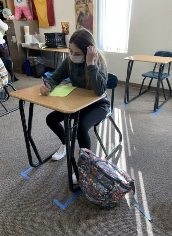 Freshman Emily Heilman sits in class with her backpack. In order to limit the spread of germs amid the COVID-19 pandemic, students have been allowed to carry backpacks instead of utilizing lockers.