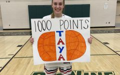 Jeffrey holds a sign made by one of her teammates after the game at Faribault High School. Many of her teammates and fans had created signs to commemorate her 1,000 point milestone.