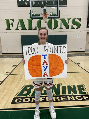 "Jeffrey holds a sign made by one of her teammates after the game at Faribault High School. Many of her teammates and fans had created signs to commemorate her 1,000 point milestone. ""She"