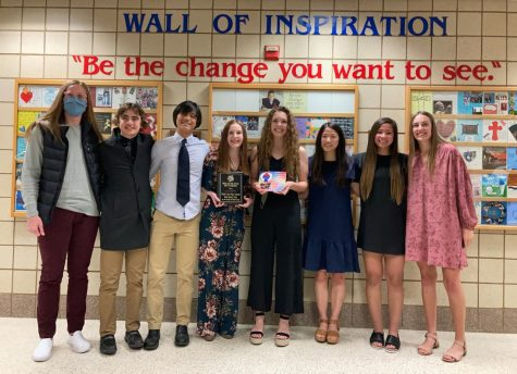 Gina Klennert, Tim Chalmers, Joseph Yoon, Kailey Boettcher, Abby Chalmers, Esther Yoon, Lucy Stay and Taya Jeffrey pose with their tile in front of the wall of inspiration. Many club members attended the event on Monday, April 12 to celebrate the club